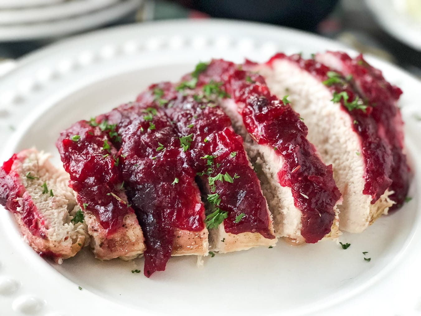 a turkey breast glazed with cranberry sauce, cut into slices and placed on a white plate