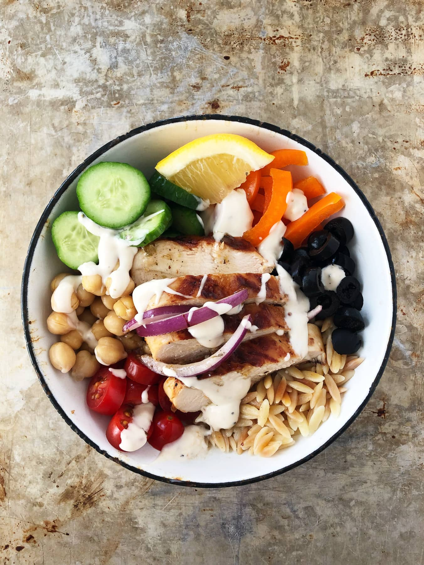 a bowl with grilled chicken, cucumbers, peppers, black olives, lemons, chick peas, tomatoes and orzo, all drizzled with Greek dressing