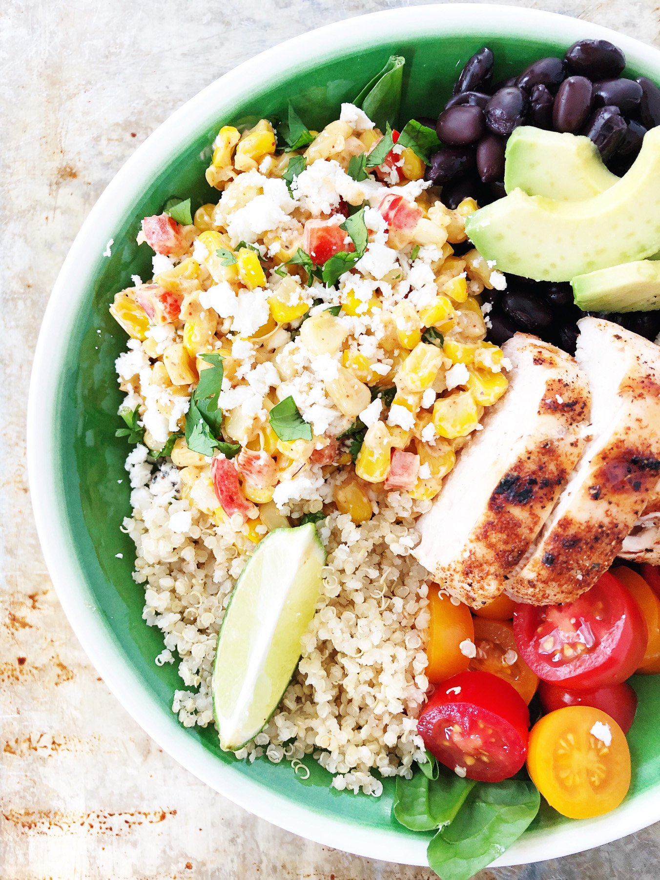 a bowl with corn, grilled chicken, diced tomatoes, avocados, quinoa and black beans