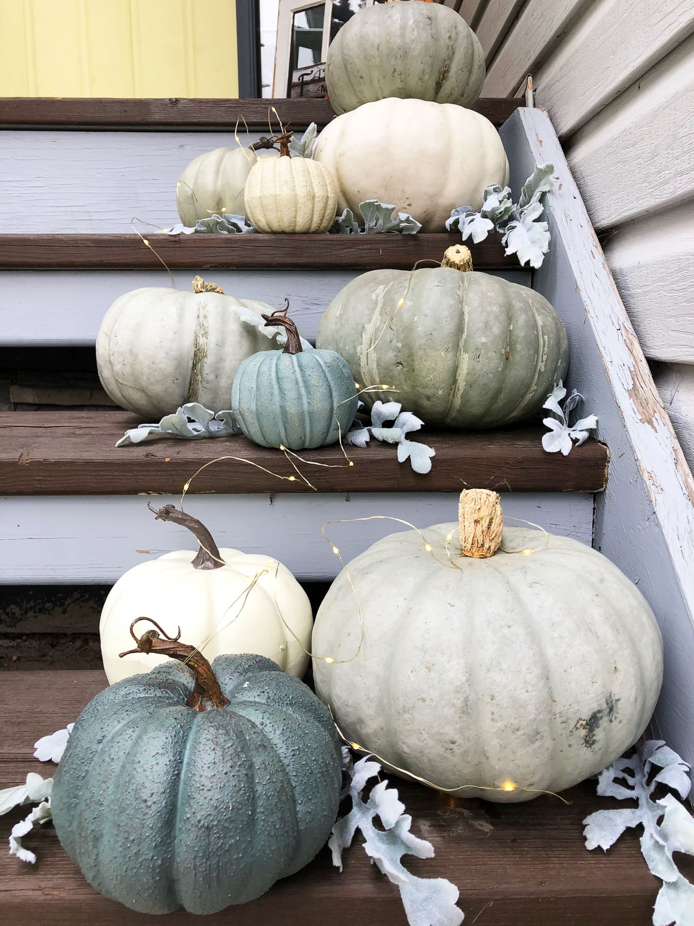 A set of stairs full of grey and blue pumpkins