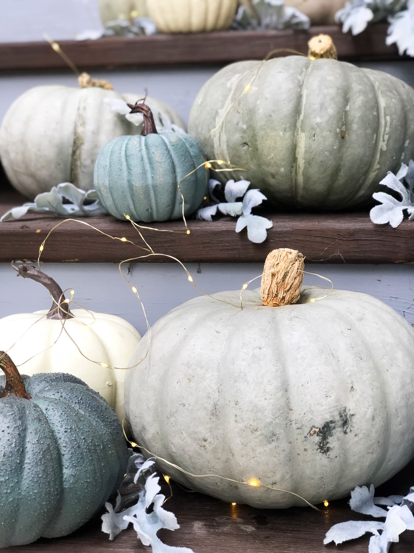 A set of stairs full of grey and blue pumpkins and twinkly lights