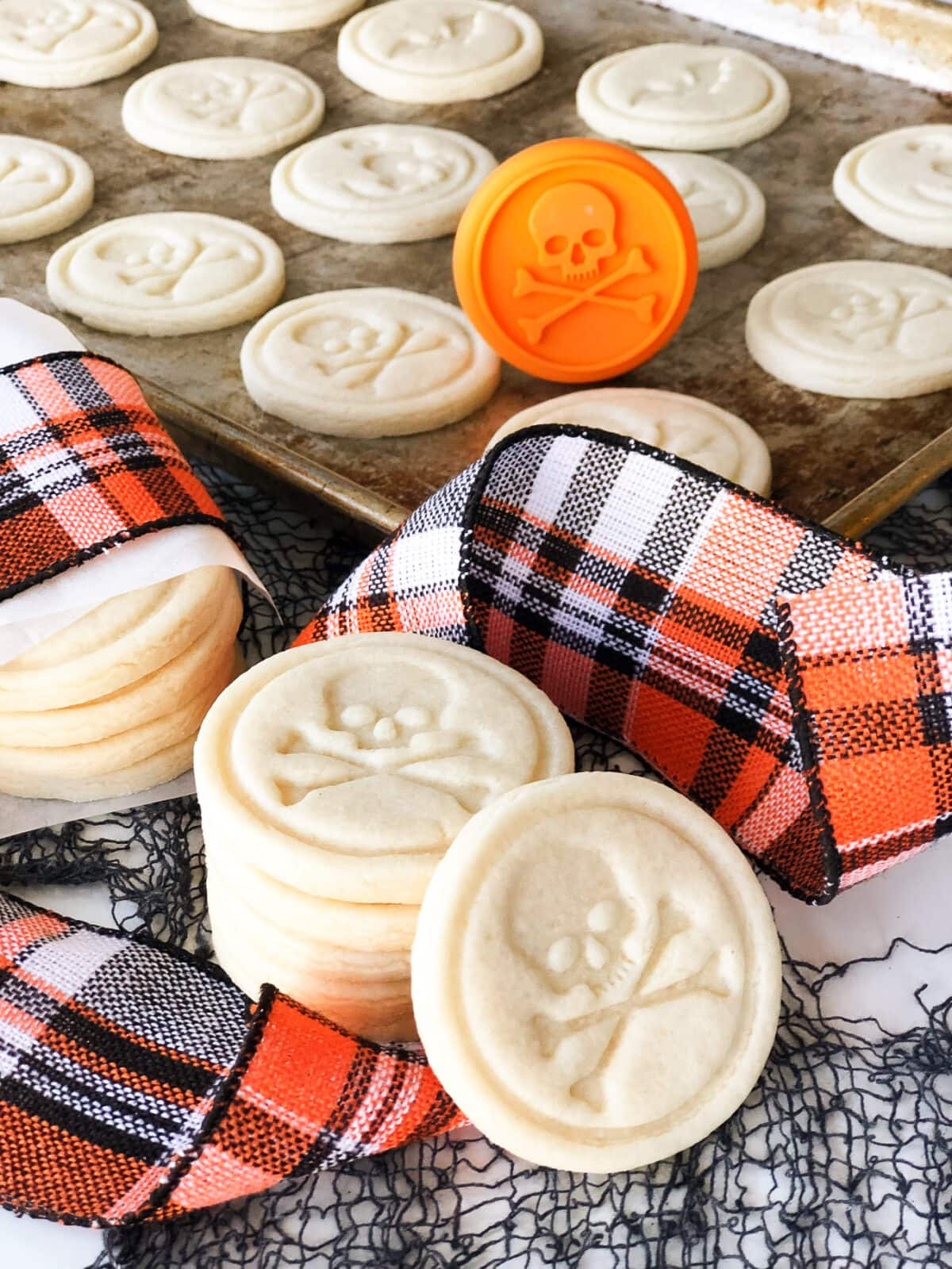sugar cookies stamped with skulls. an orange and black plaid ribbon runs across the cookies