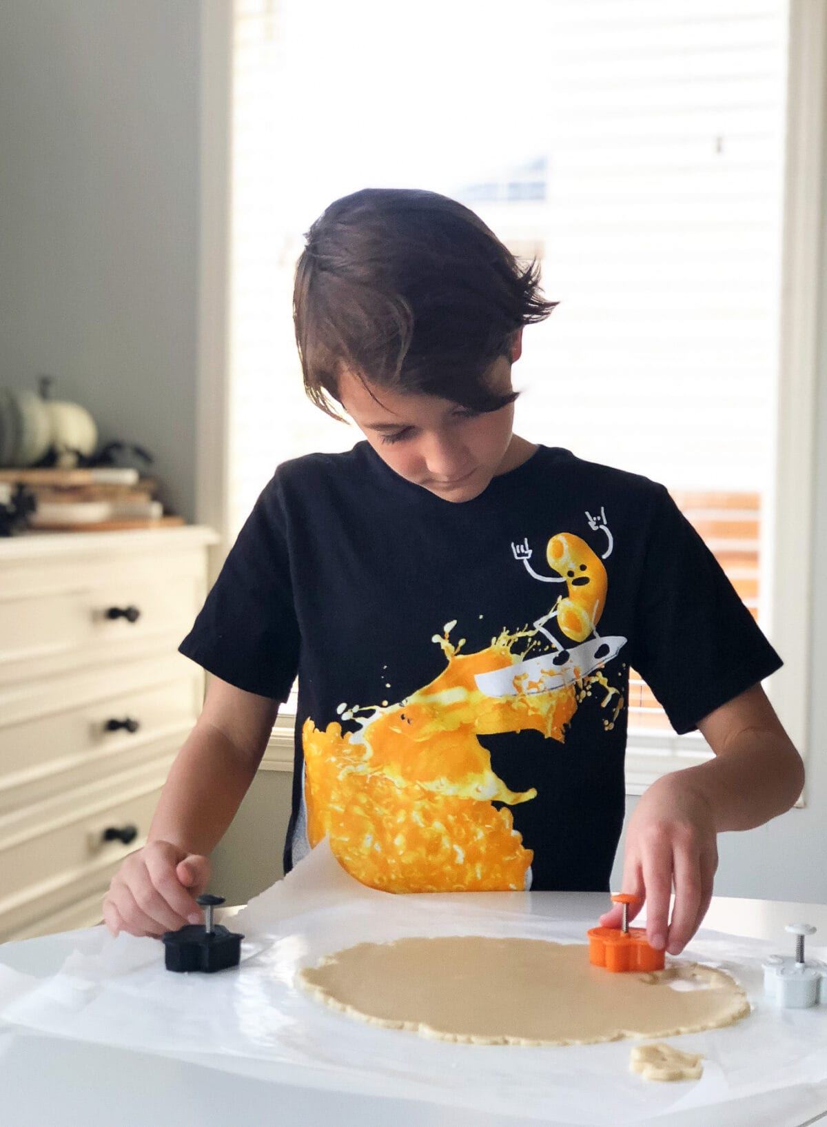 A little boy using a cookie stamp to cut out sugar cookie