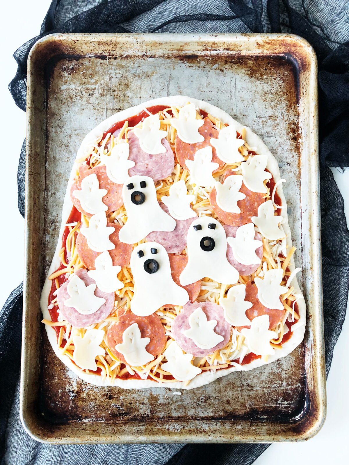 a top down view of an unbaked pizza with ghosts made out of cheese. they have eyes and mouths made out of black olives