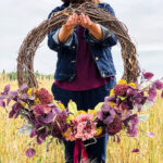A floral fall wreath held in a wheat field