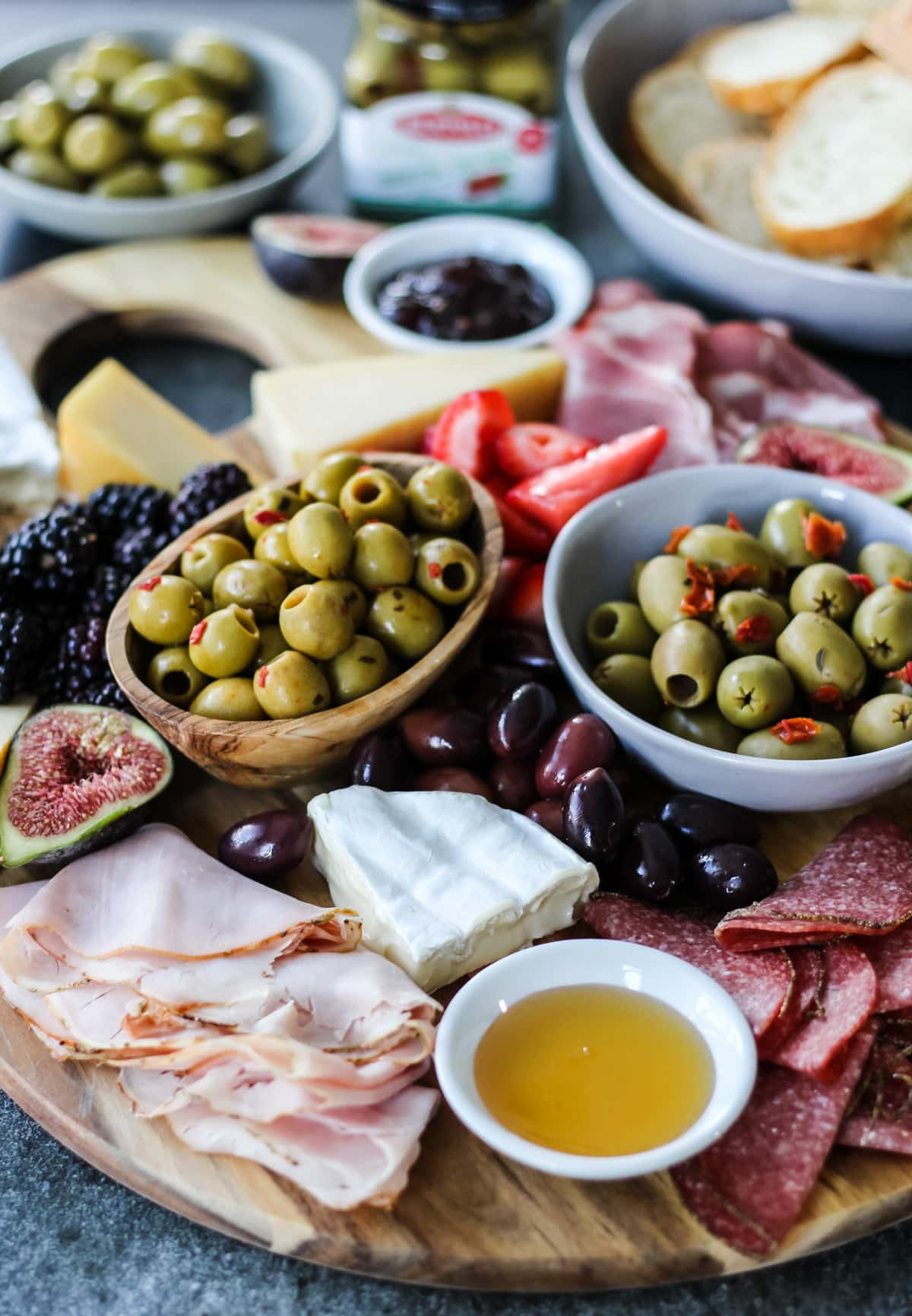 a charcuterie board loaded with green olives, kalamata olives, fresh figs, brie cheese, deli meats, honey, cheese and blackberries