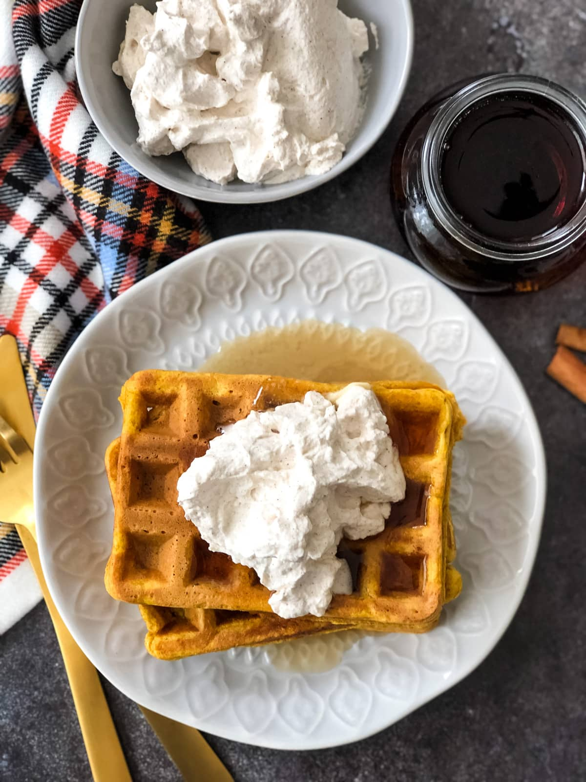 A top down view of a plate of Pumpkin Pie Waffles with Cinnamon Whipped Cream