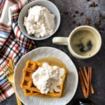 Pumpkin Pie Waffles with Cinnamon Whipped Cream set out on the breakfast table