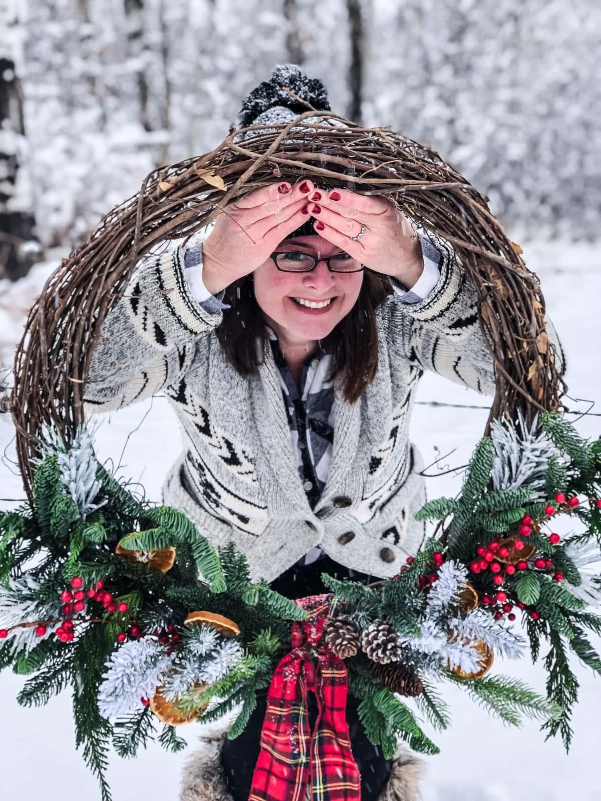 A woman holding a giant Christmas wreath