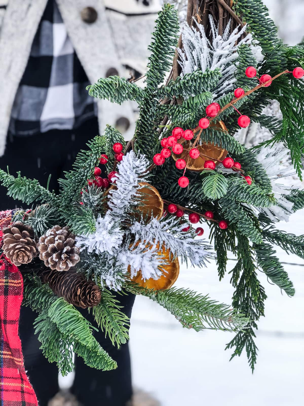 A close up of a fresh evergreen Christmas wreath with pine cones, red berries and dried oranges