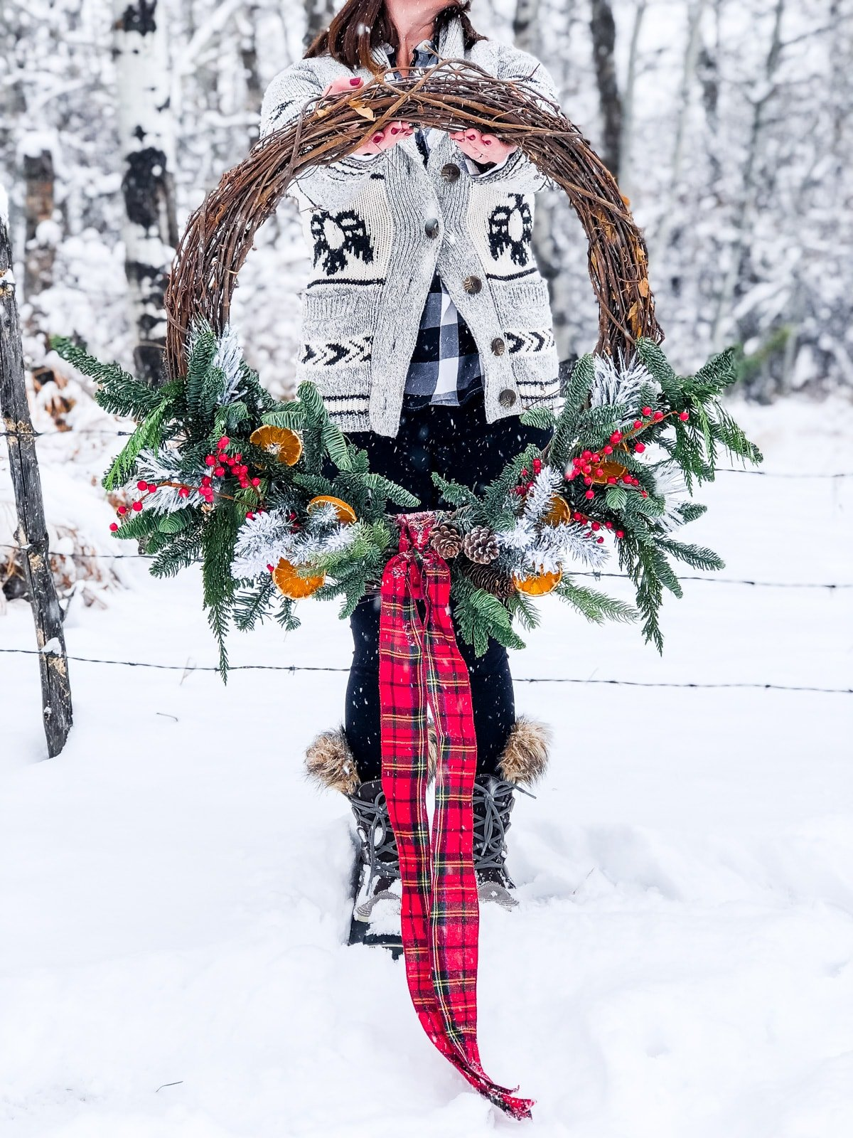 A woman holding a Giant Evergreen Wreath with Plaid and Dried Oranges