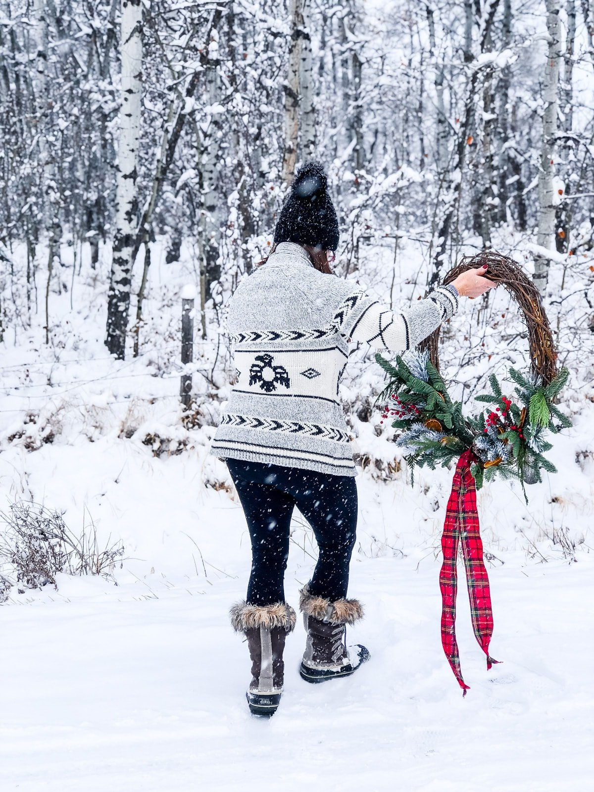 A woman walking away into a snowy forest while holding a Giant Evergreen Wreath with Plaid and Dried Oranges