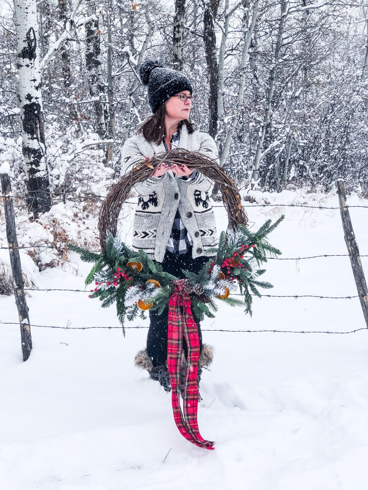 A woman holding a giant Christmas wreath while out in a snowy forest
