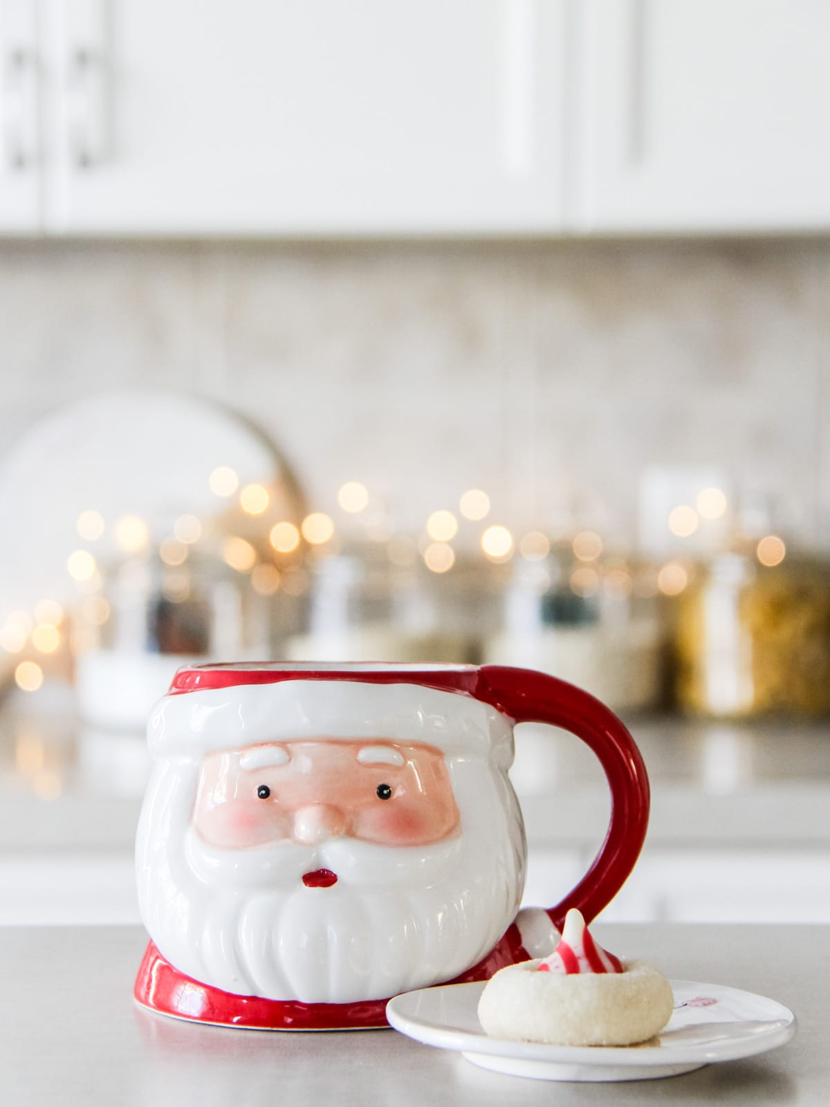 A Santa mug on a kitchen counter with twinkly lights in the background