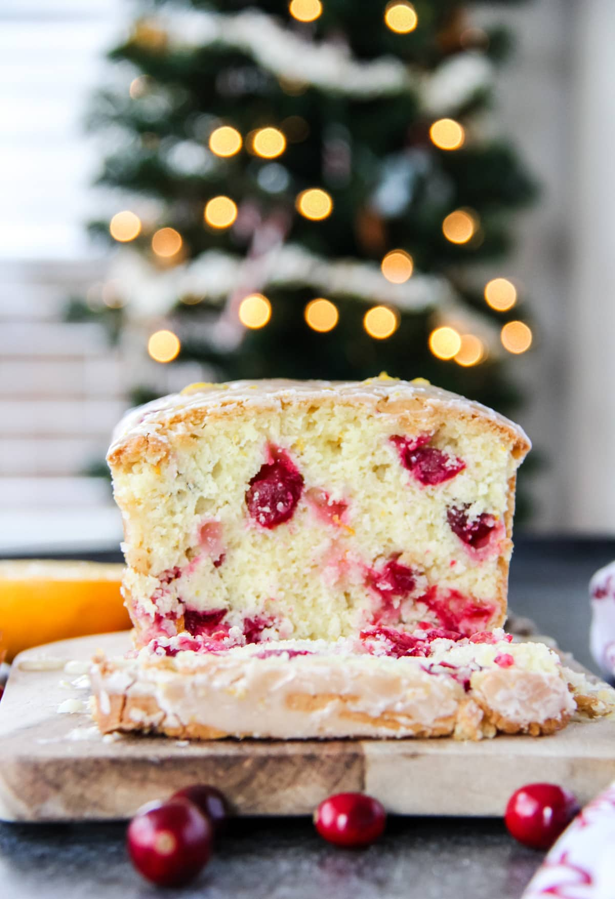 a close up of a slice of cranberry orange loaf. In the background is a tree with Bokeh lights