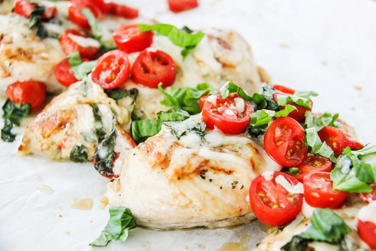 simple summer meals: a side view of cooked chicken topped with fresh tomatoes, fresh chopped basil and melted mozzarella