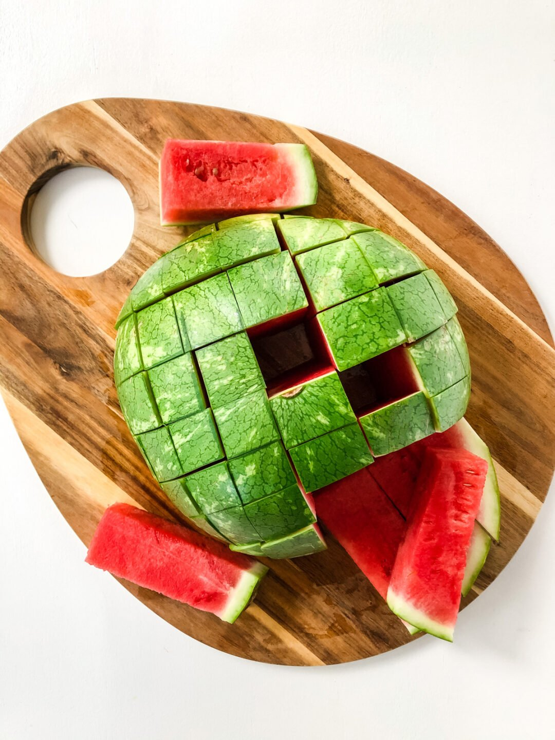 A board with watermelon cut into individual serving sticks
