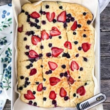 A tray of sliced Sheet Pan Pancakes, with strawberries and blueberries