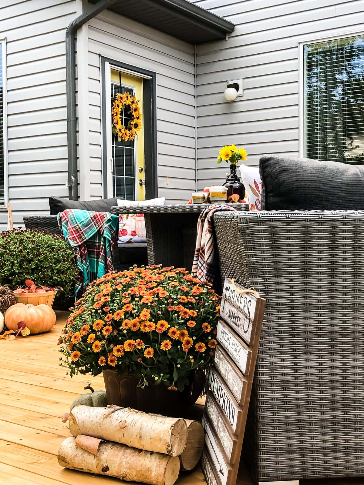 An outdoor deck decorated for fall with pumpkins, candles, mums, blankets and pillows