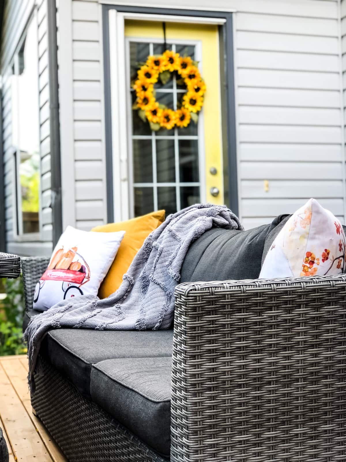 An outdoor couch with fall pillows and blankets
