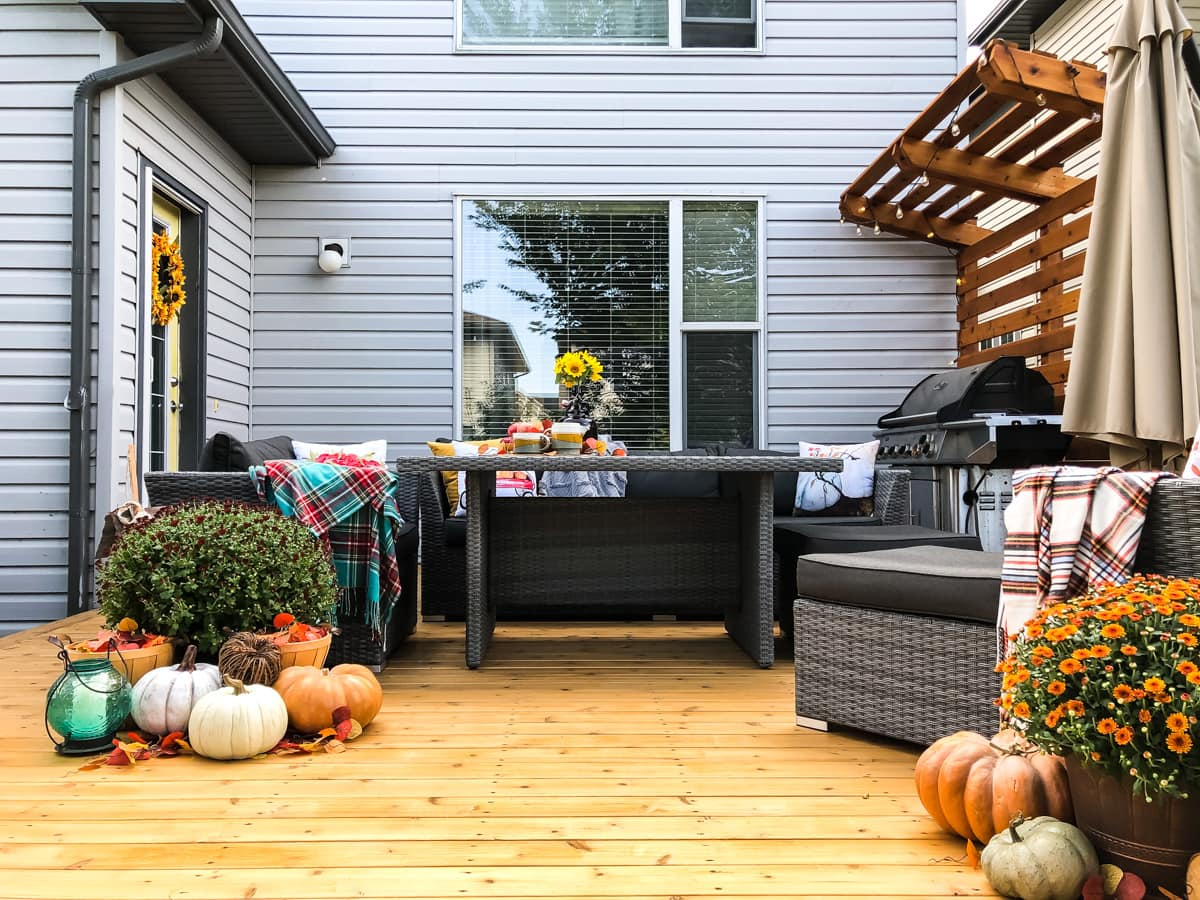 An outdoor deck decorated for fall with pumpkins, candles and mums