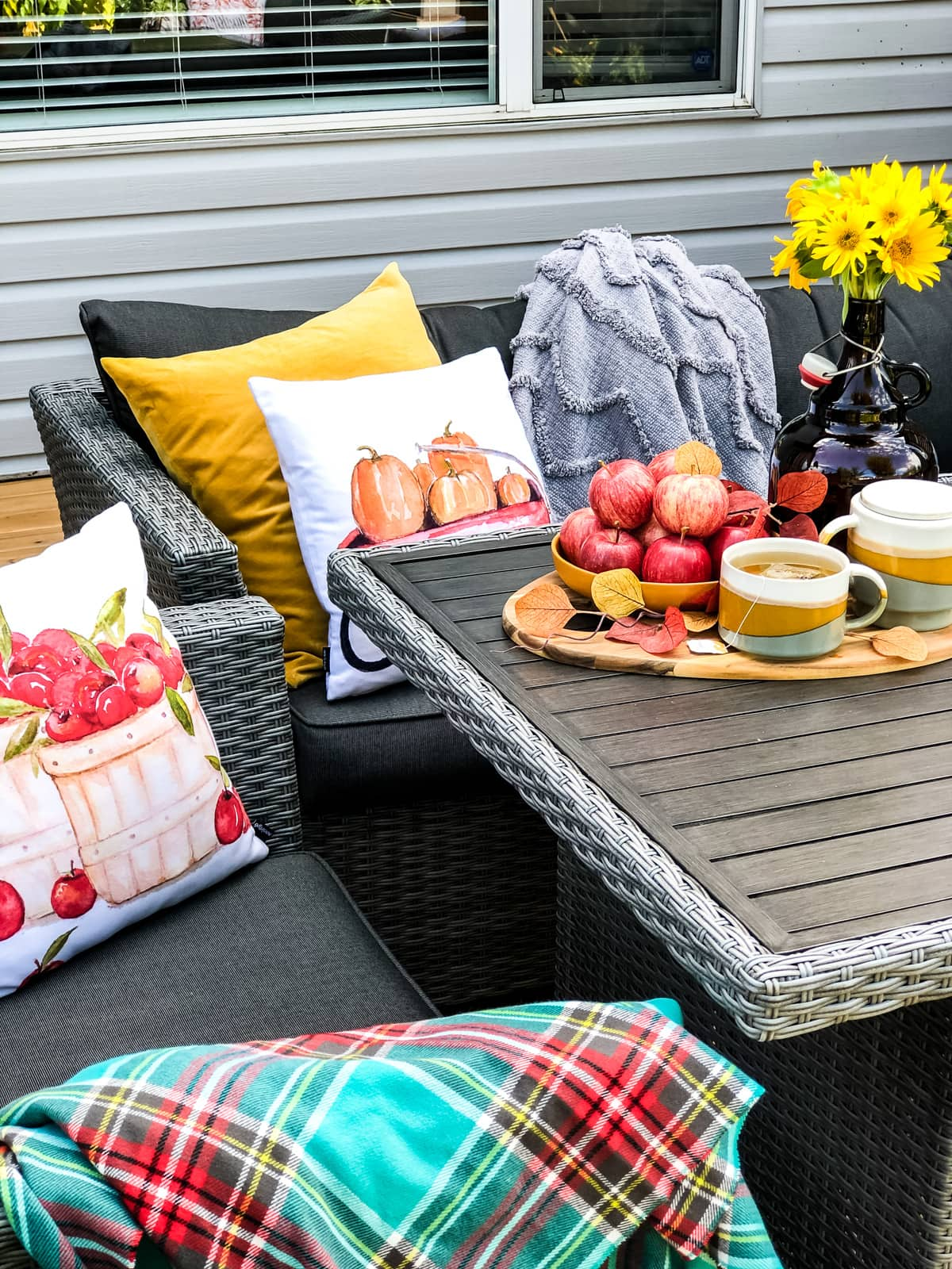 An outdoor table setting with a tray of apples and tea