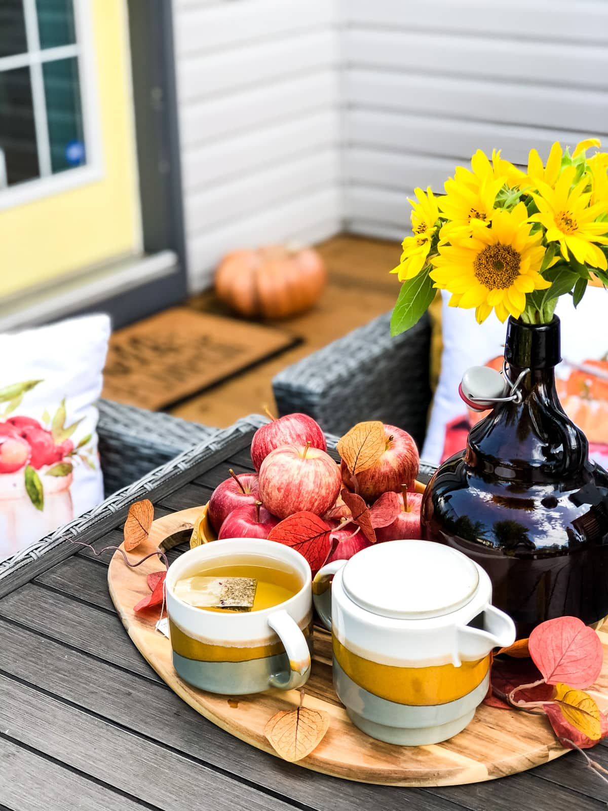 A tray of apples, sunflowers and tea