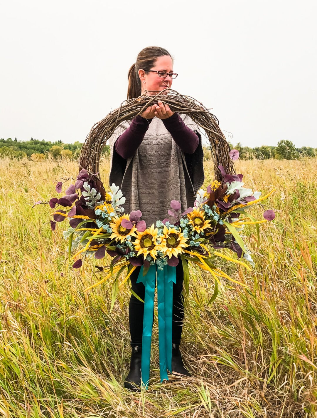 A fall flower wreath being held out in a field