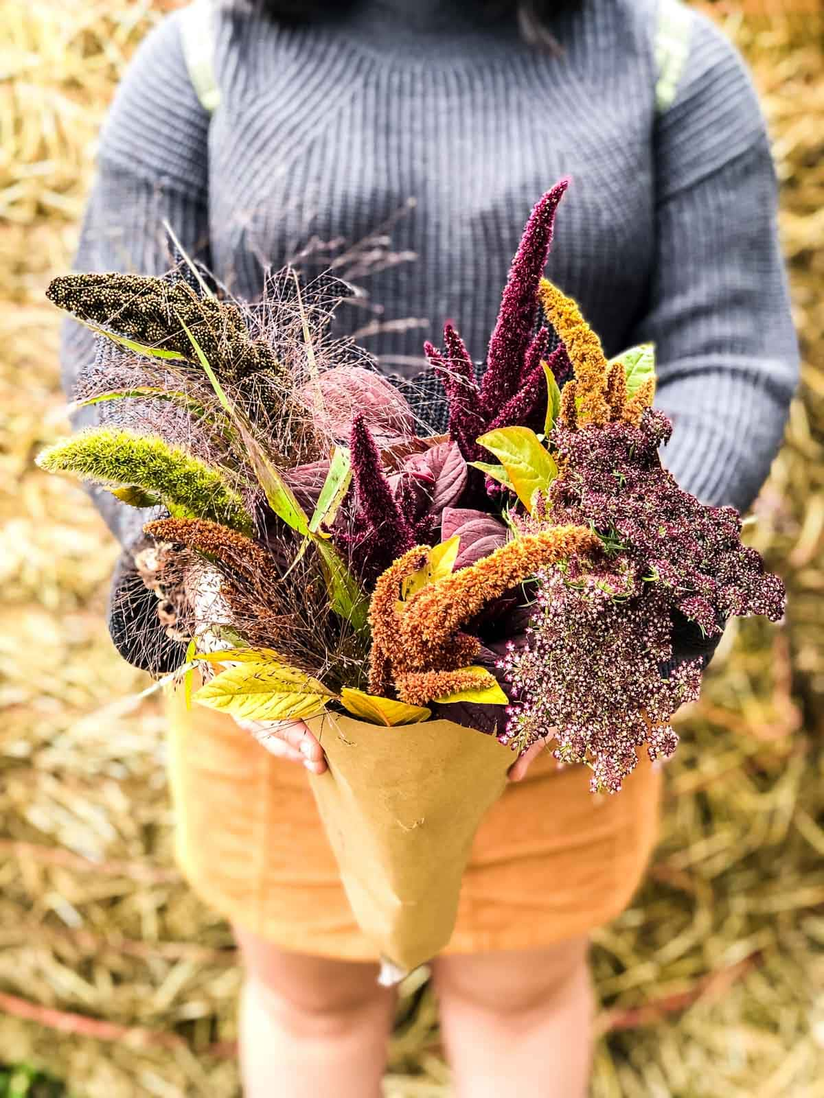 A bunch of fall grasses being held in a brown paper wrapping