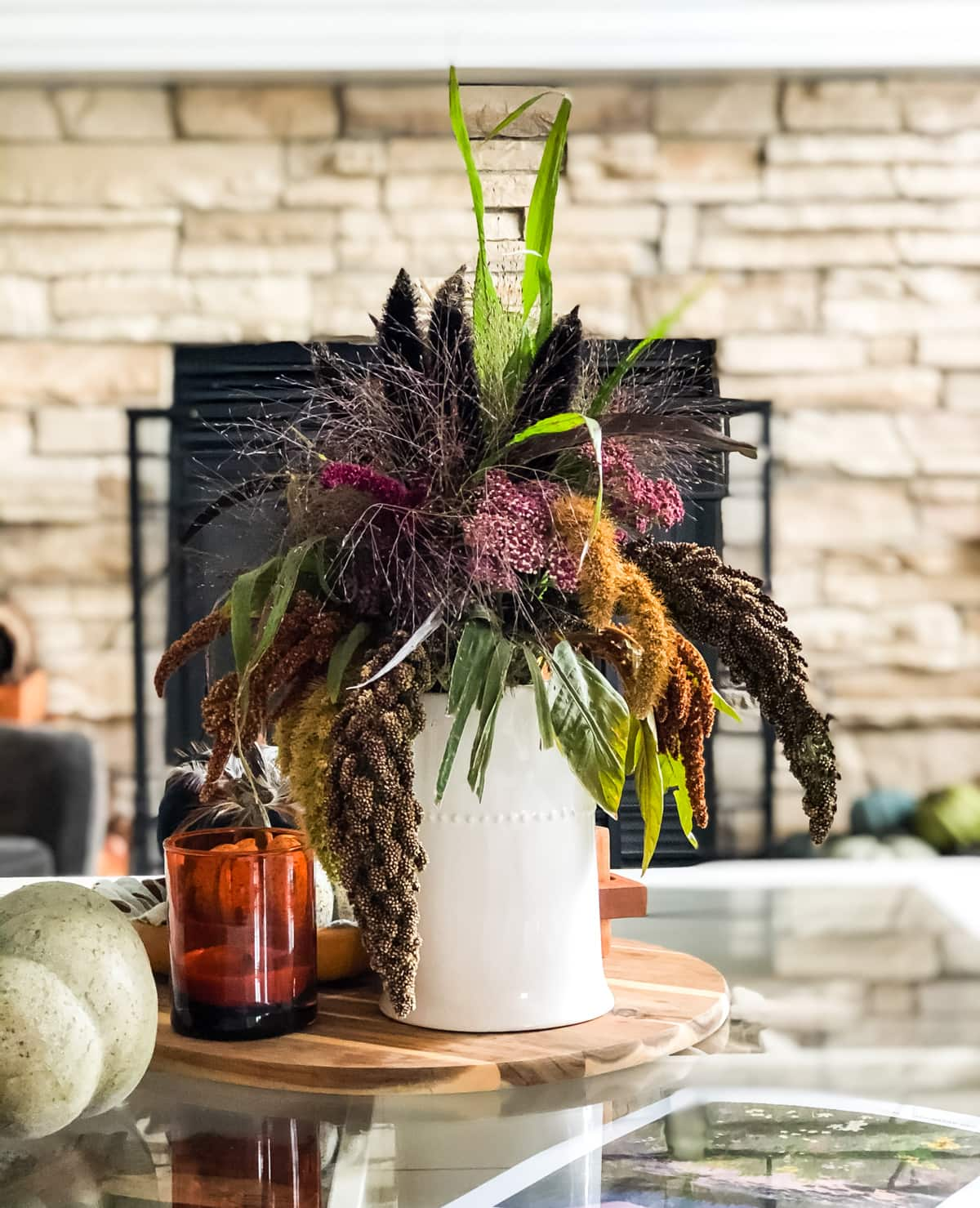 A Fall Flower Arrangement in a cream vase sitting on a coffee table