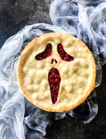 A top down view of a baked raspberry pie with a Scream face crust