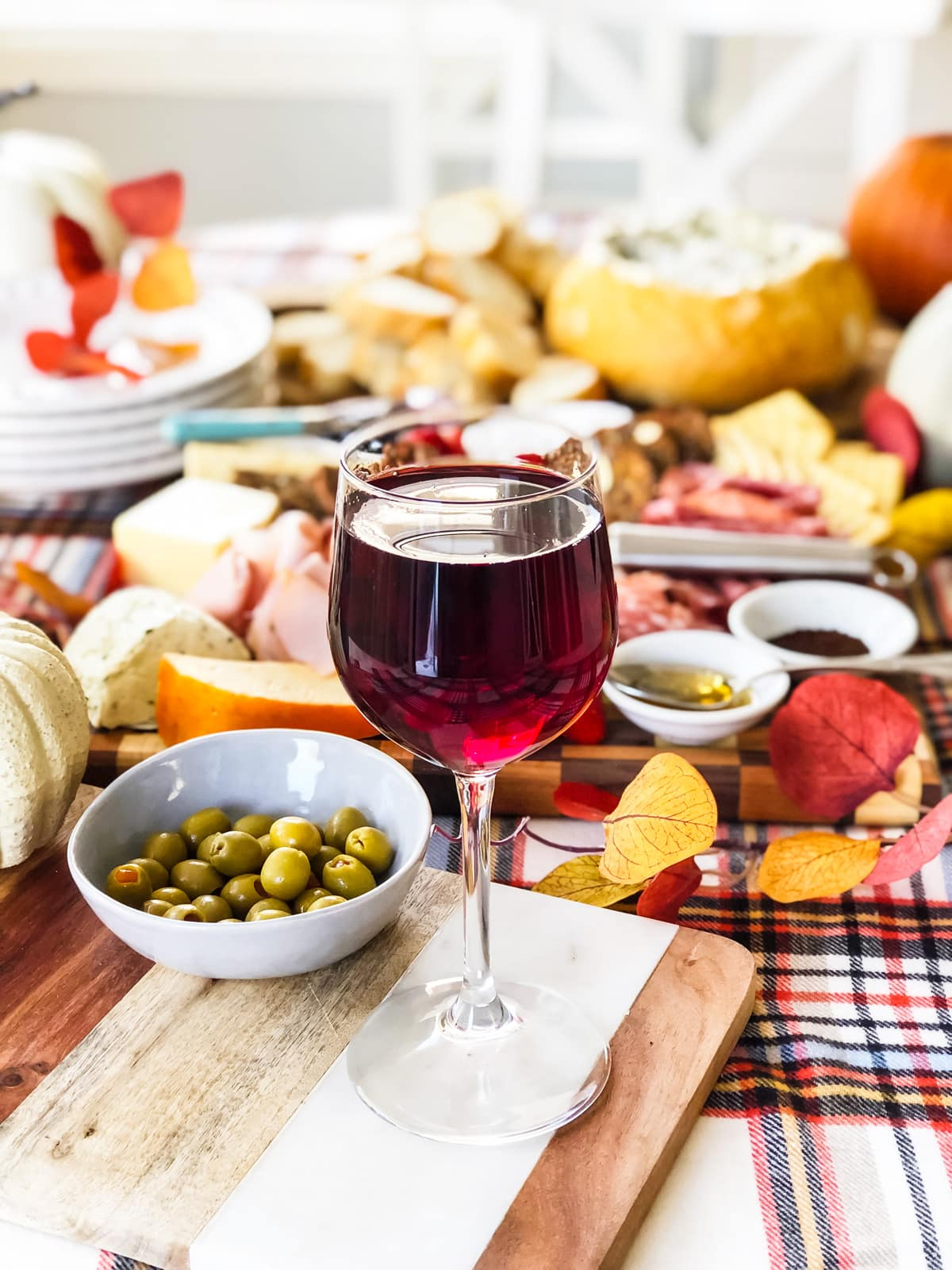 A glass of wine on a table full of delicious charcuterie, appetizers, dips and fruit