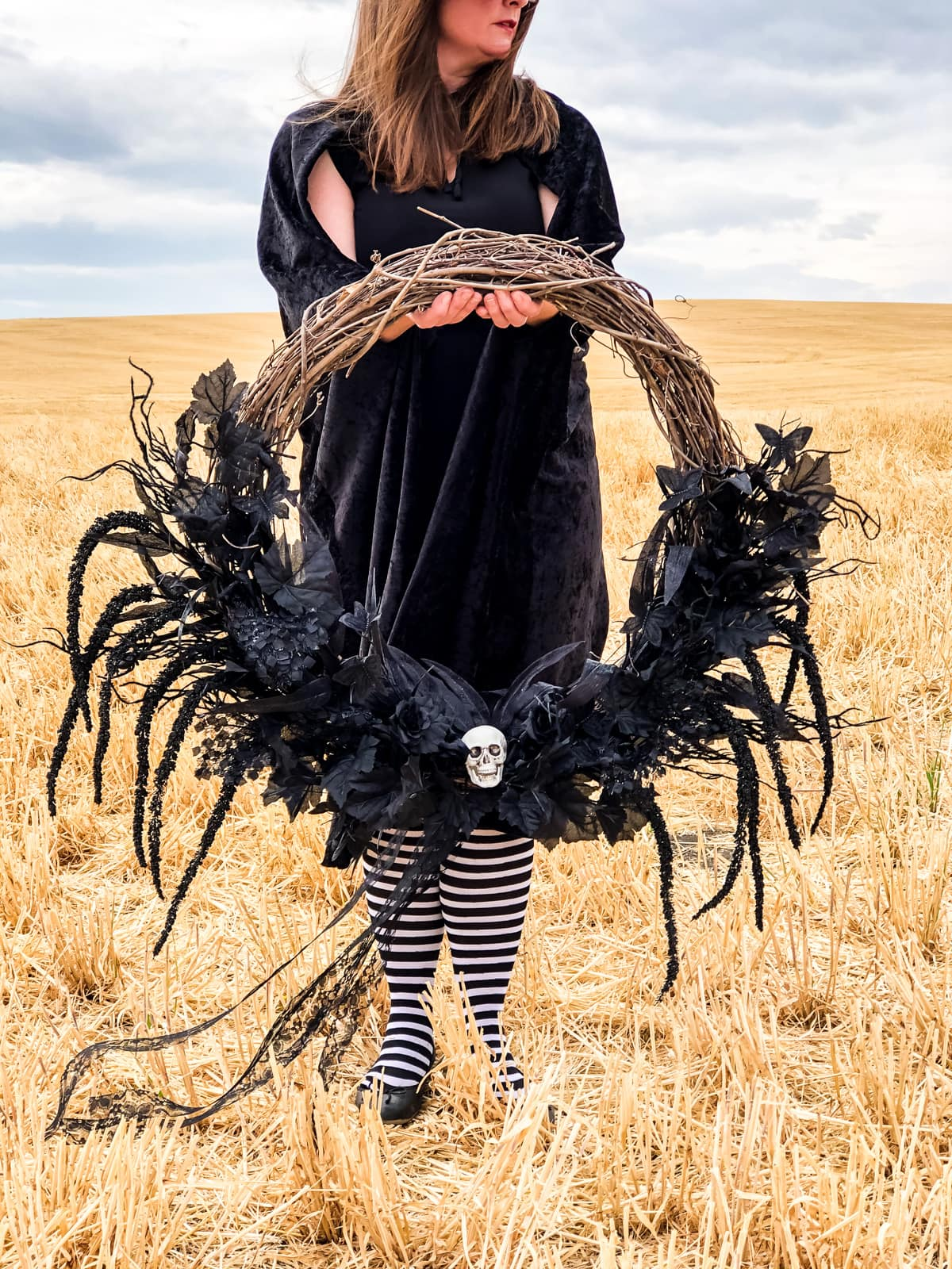 A picture of a lady in a wheat field holding a black Halloween wreath
