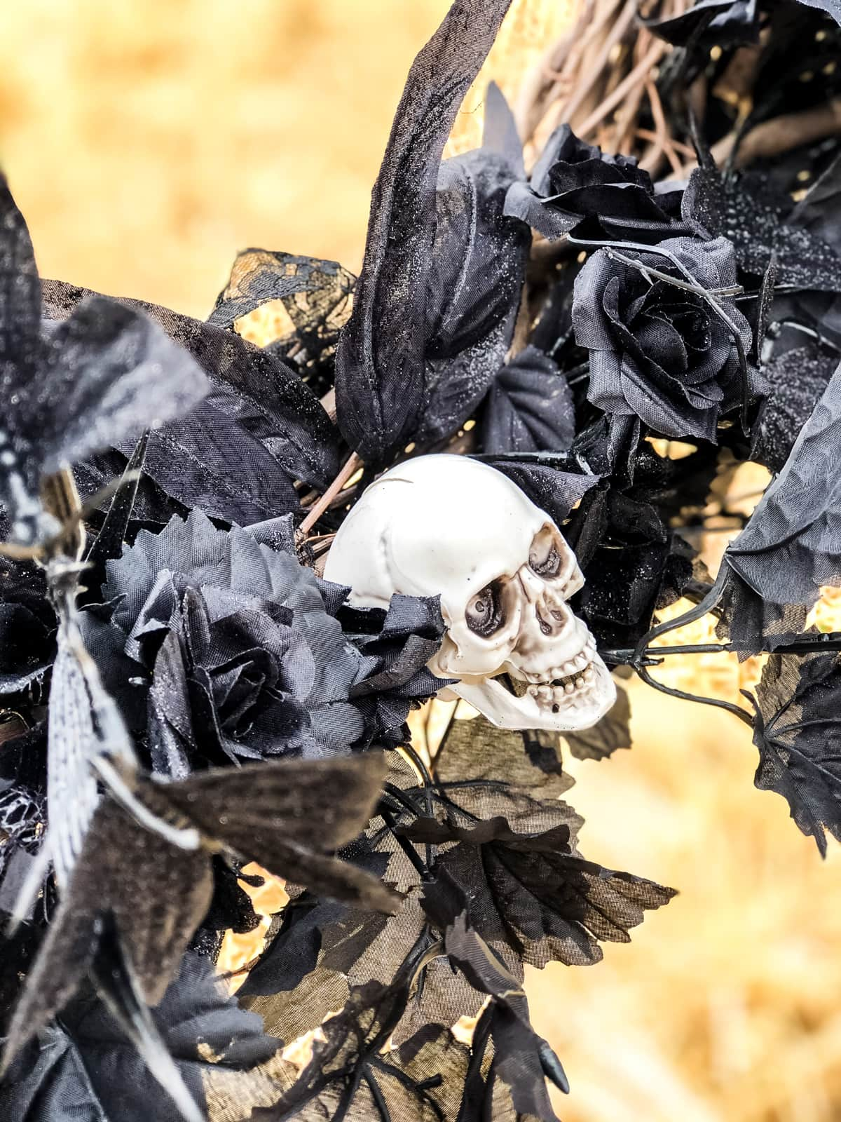 A close up of black floral stems and a decorative skull