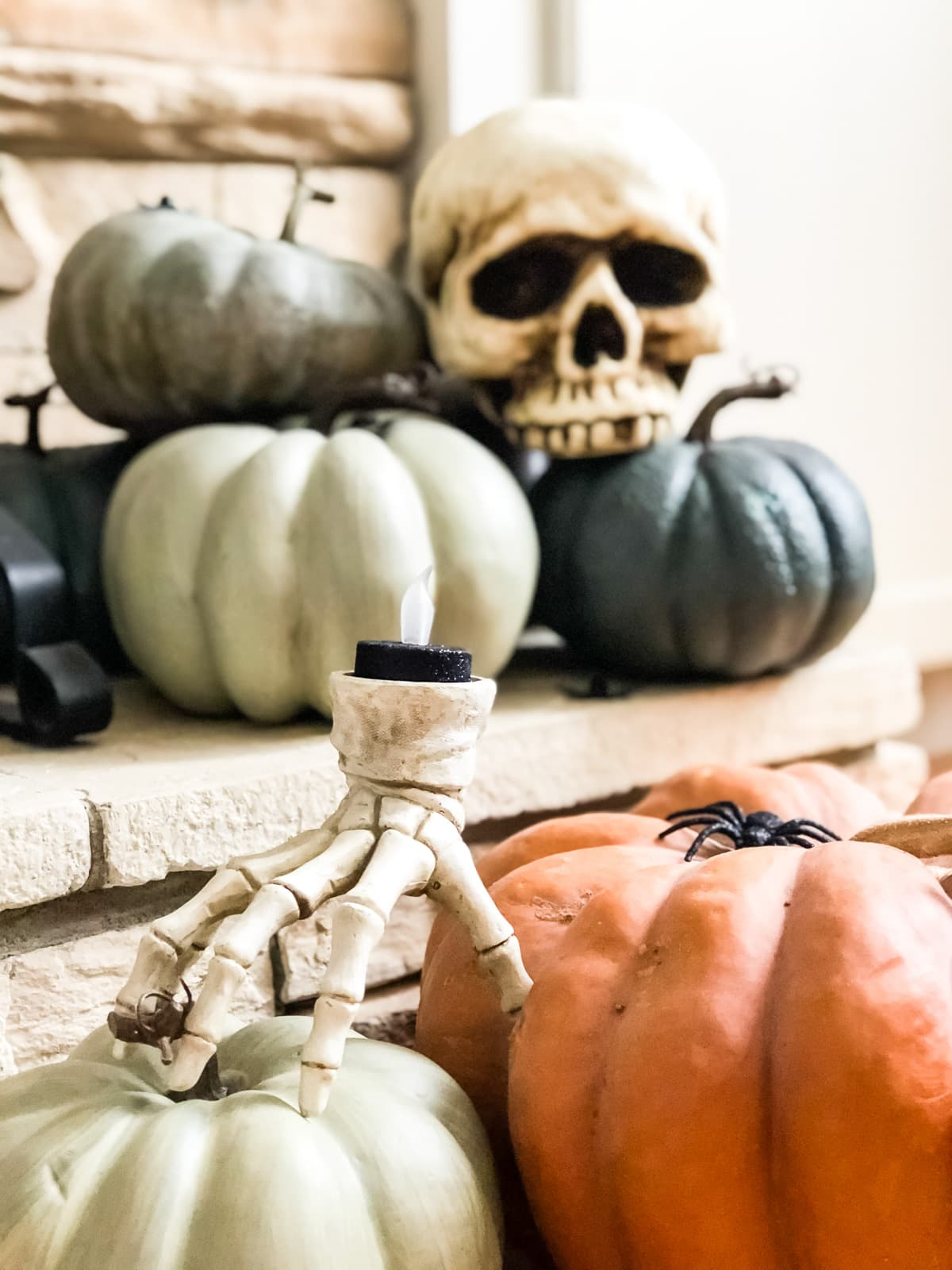 A skeleton hand candle holder among pumpkins