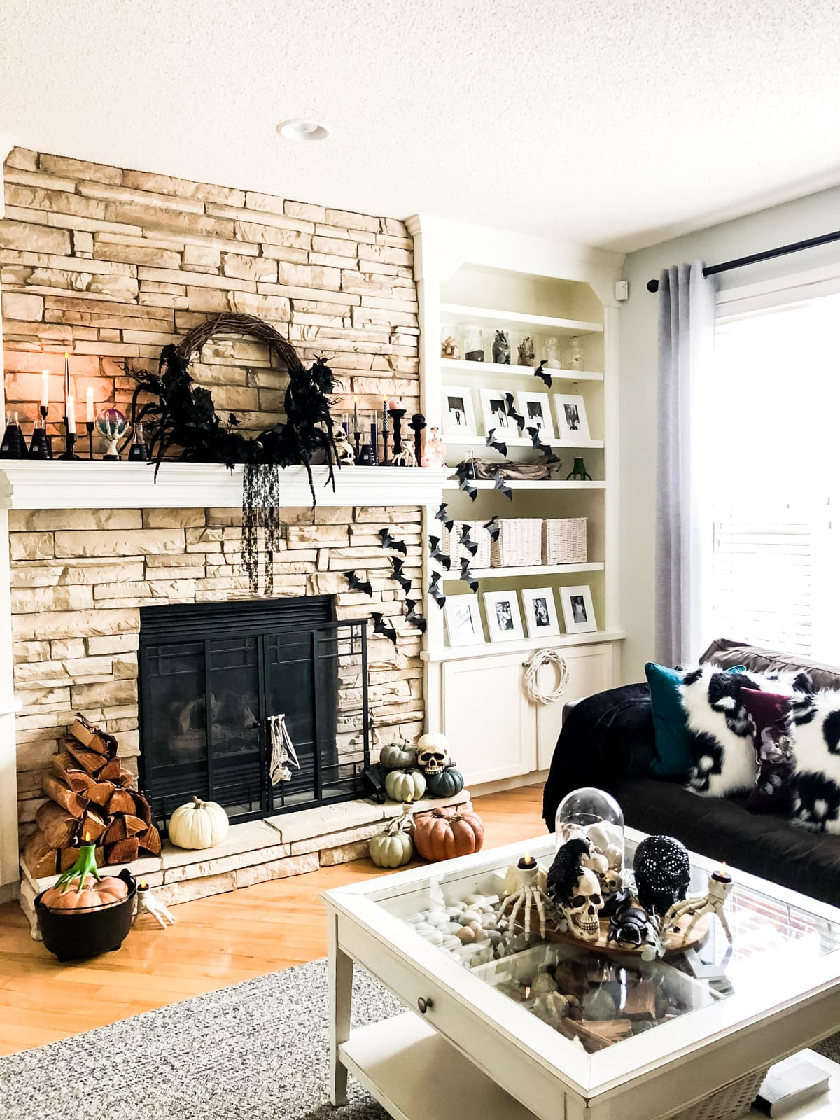 A living room decorated for Halloween with a wreath, plastic bats, pumpkins and skulls