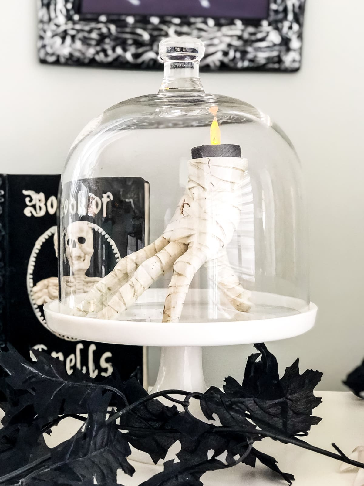 A mummy hand candle holder under a cloche