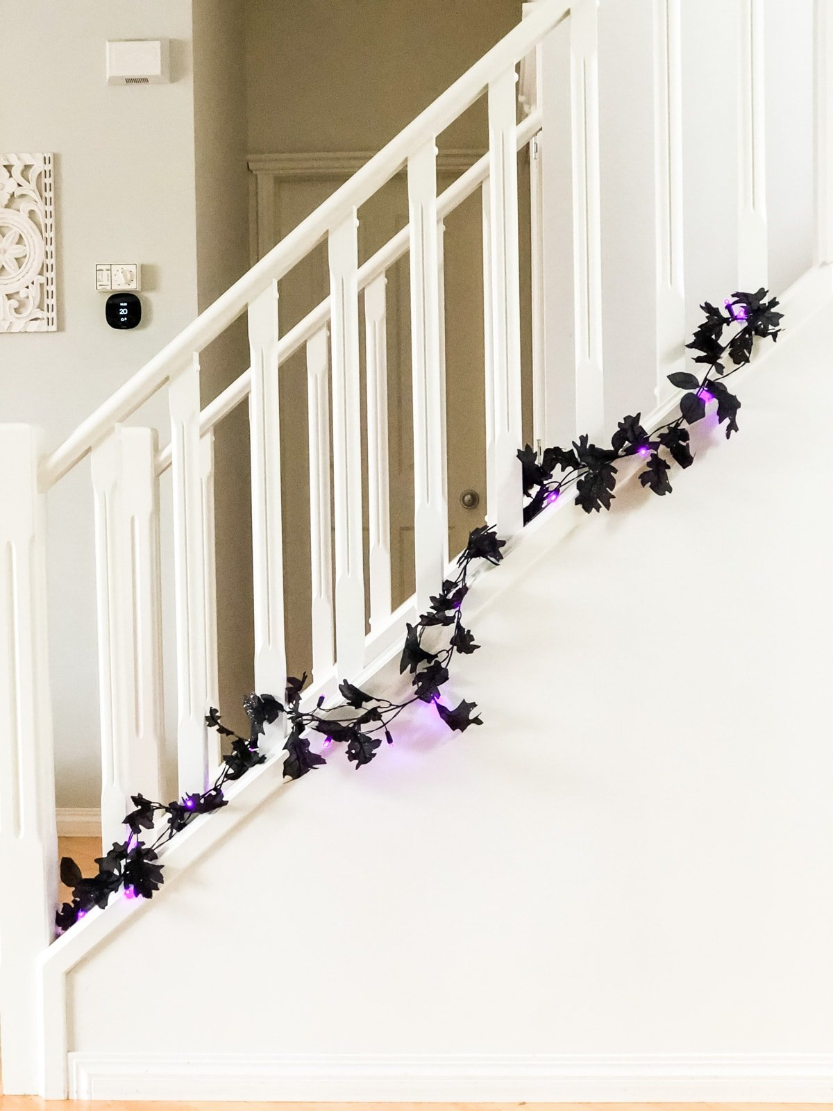 A staircase decorated with a black leaf garland and purple lights
