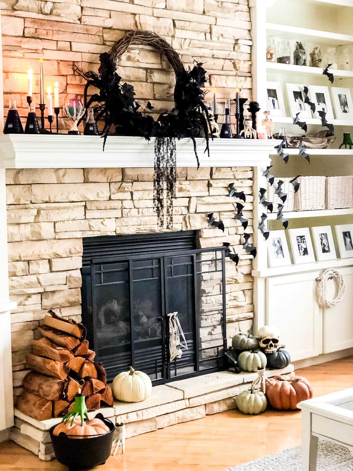 Fireplace mantel decorated for Halloween with a wreath and bats