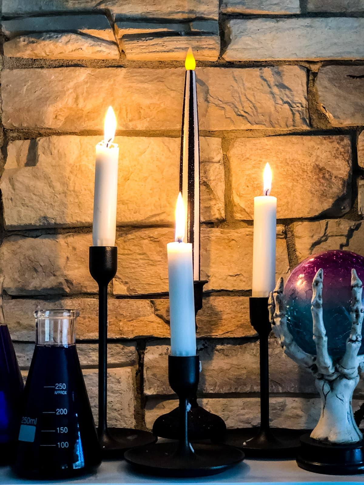 Candles lit on a fireplace mantel