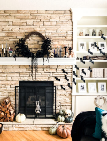 A fireplace mantel decorated for Halloween with a wreath, candles and bats
