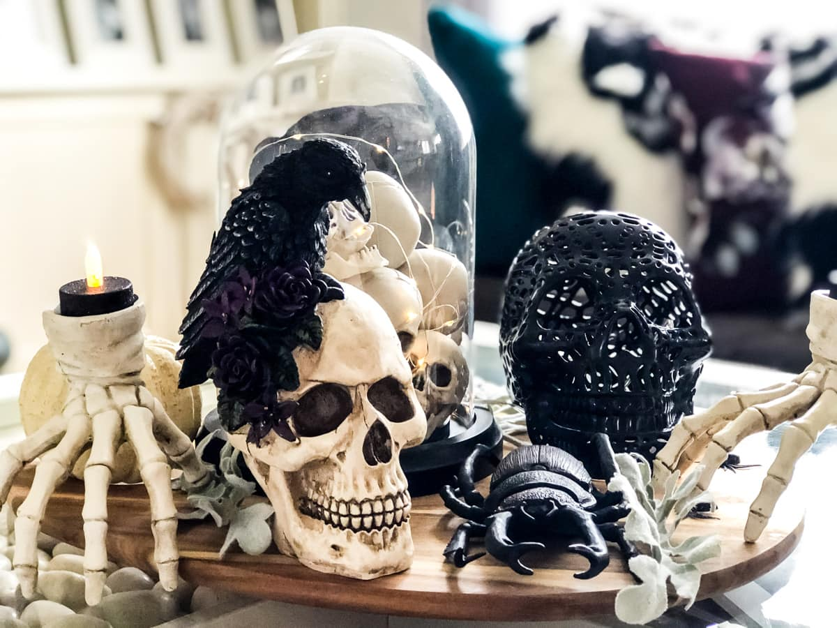 A table with Halloween skulls, bugs and skeleton hand candle holders