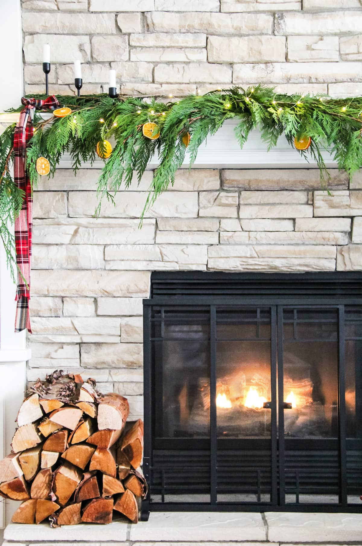 a view of half of a fireplace mantel decorated with fresh cedar boughs, orange slice ornaments, string fairy lights and plaid ribbon. With a fire roaring in the fireplaces and a stack of wood on the left