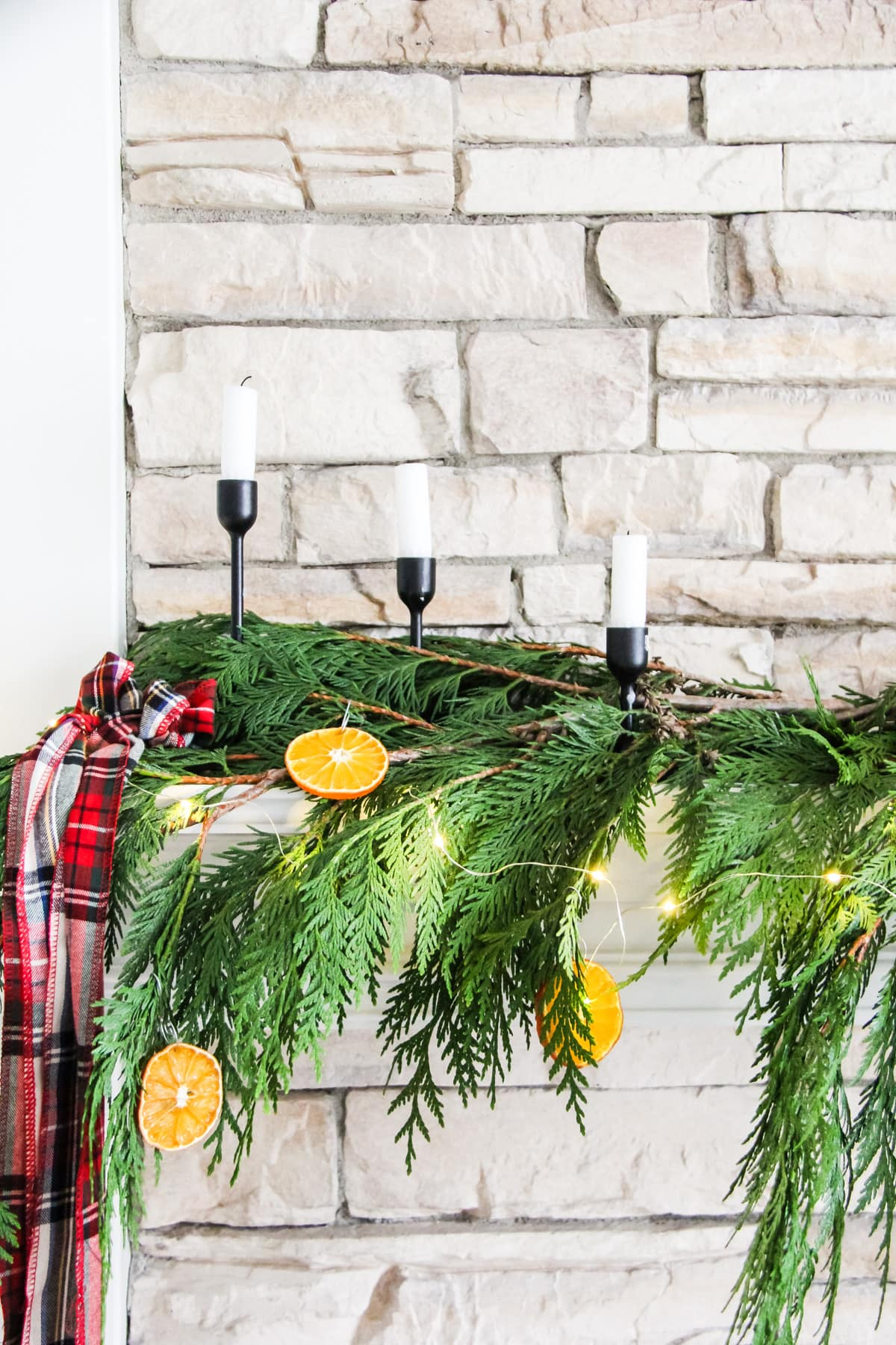 a close up view of half of a fireplace mantel decorated with fresh cedar boughs, orange slice ornaments, string fairy lights and plaid ribbon