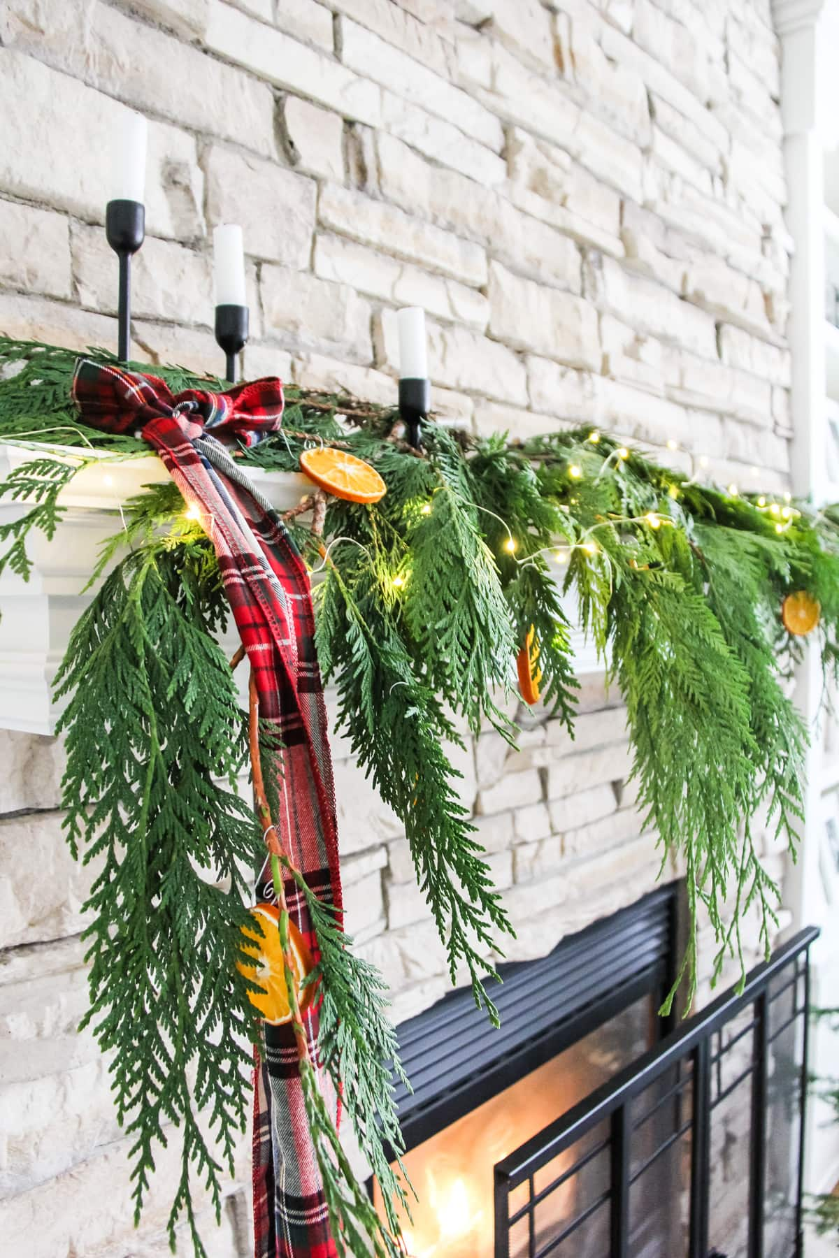 fresh evergreen cedar branches strewn on a mantel and decorated with string fairy lights, orange slice ornaments, plaid ribbon and three candlesticks