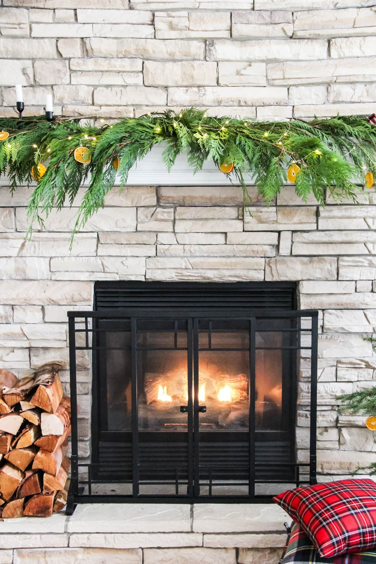 a fireplace mantel decorated with fresh cedar boughs, orange slice ornaments, string fairy lights and plaid ribbon. With a fire roaring in the fireplaces and a stack of wood on the left