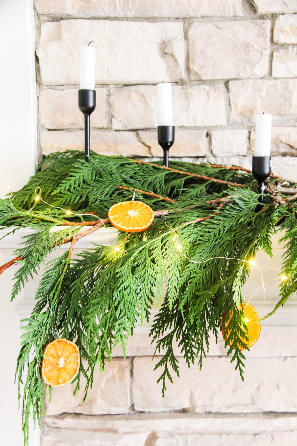 a close up of fresh cedar greens, orange slice ornaments, fairy lights and three candles