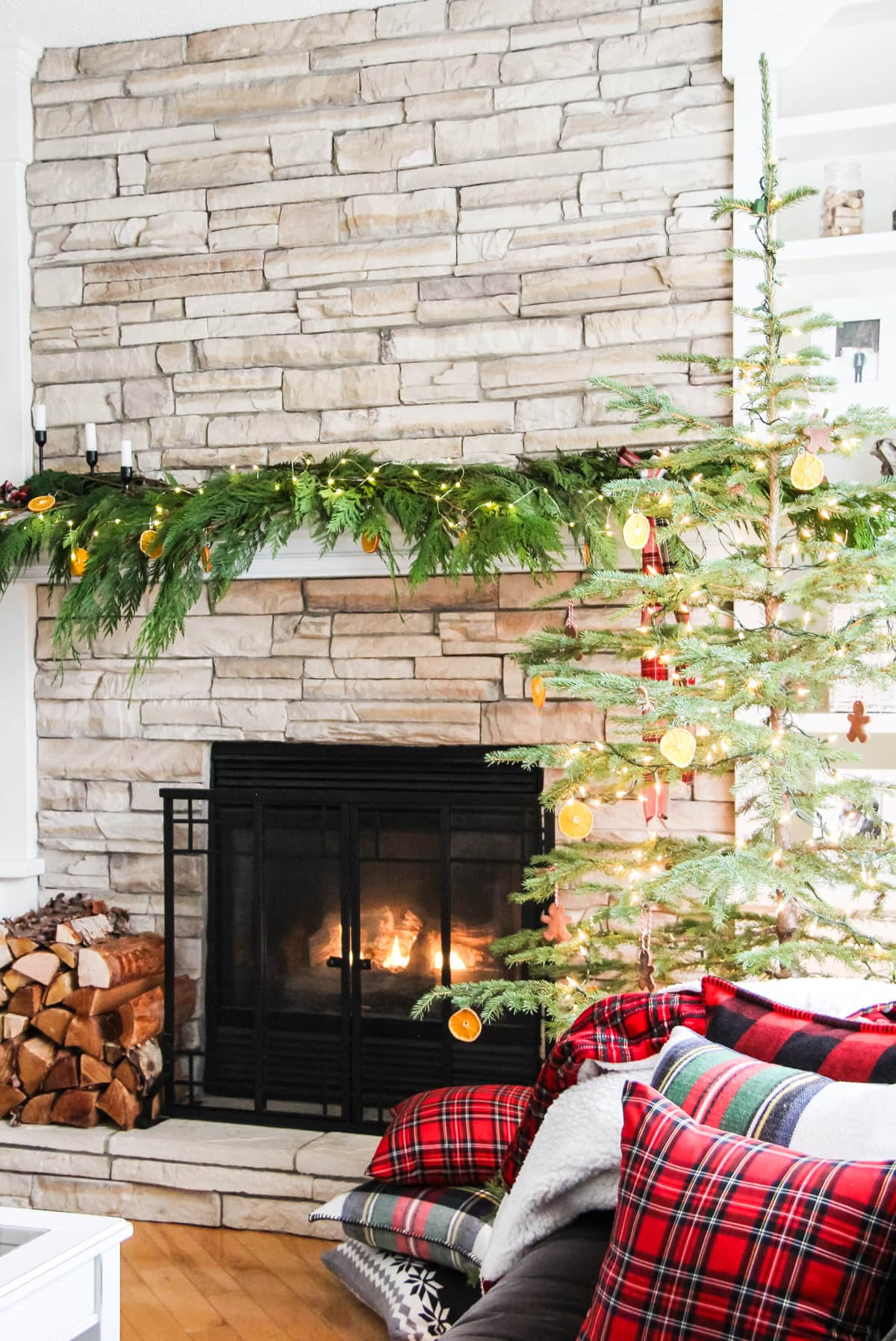 a fireplace mantel decorated with fresh cedar boughs, orange slice ornaments, string fairy lights and plaid ribbon. With a fire roaring in the fireplaces and a stack of wood on the left and a Christmas tree on the right