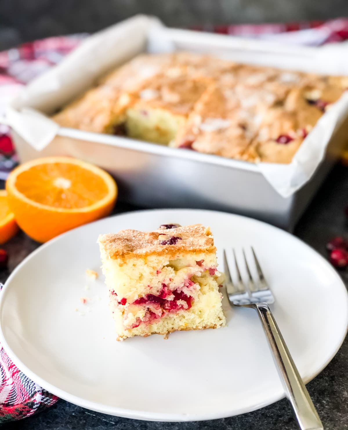 A close up of a cut square of Cranberry Orange Breakfast Cake on a plate with a fork