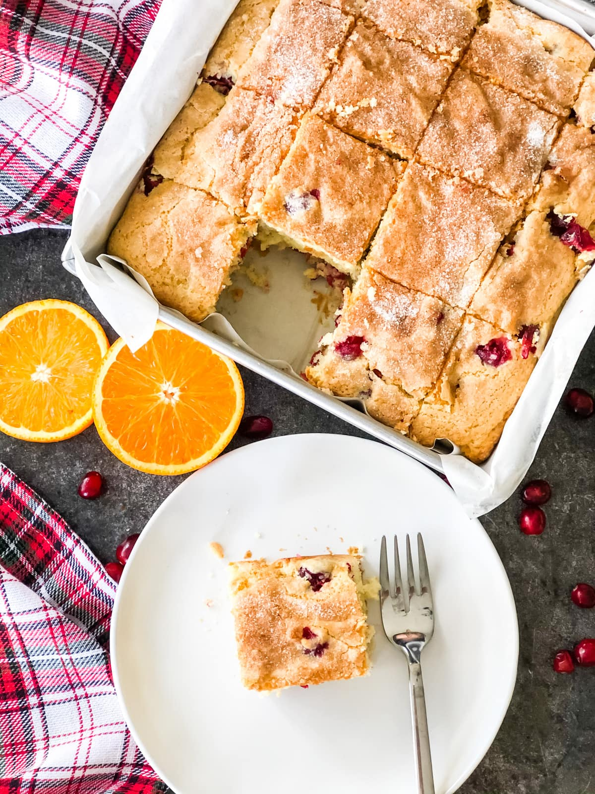 A top down view of a Cranberry Orange Breakfast Cake cut into squares with a piece of cake on a plate